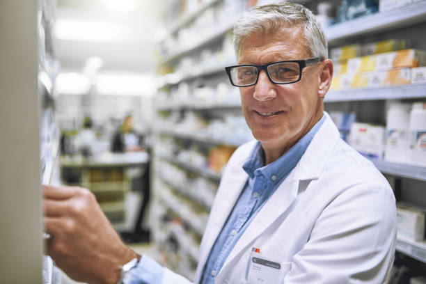 Stocking up on some new meds Portrait of a cheerful mature male pharmacist getting medication from a shelf while looking at the camera in a pharmacy prescription meds stock pictures, royalty-free photos & images