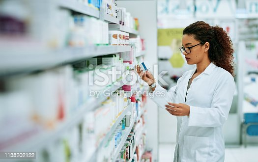 Shot of a young woman filling a prescription while working in a chemist