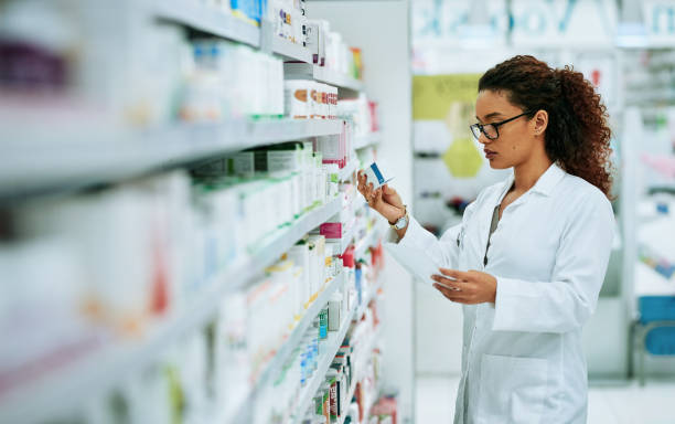 Stocking up on the best products in the pharmaceutical industry Shot of a young woman filling a prescription while working in a chemist chemist stock pictures, royalty-free photos & images
