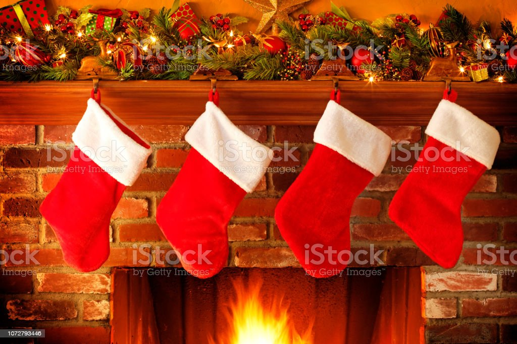 Stockings Hanging From Christmas Mantelpiece Above Roaring Fireplace stock photo