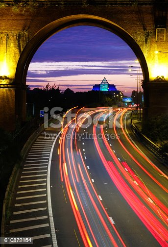 Vertical version of this image taken at dusk with commuter traffic on the motorway passing under the Victorian viaduct heading towards the modern glass and steel structure ahead.