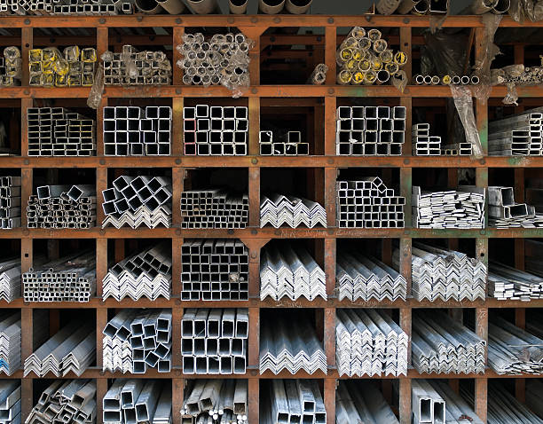Stocks in a Warehouse Square compartments made of rusty iron beams used as storage racks for aluminum pipes of various shapes and sizes. distribution center stock pictures, royalty-free photos & images