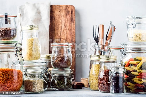 Stocks or set of cereals, pasta, groats, organic legumes and useful seeds in glass jars. Vegan source of protein and energy resources. Healthy vegetarian food. Domestic life scene. Gray kitchen table. Selective focus