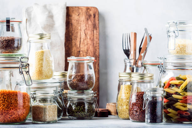 stocks or set of cereals, pasta, groats, organic legumes and useful seeds in glass jars. vegan source of protein and energy resources. healthy vegetarian food. domestic life scene. gray kitchen table. selective focus - riso cereale foto e immagini stock