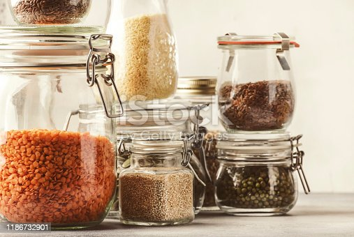 Stocks or set of cereals, pasta, groats, organic legumes and useful seeds in glass jars. Vegan source of protein and energy resources. Healthy vegetarian food. Domestic life scene. Gray kitchen table background. Selective focus