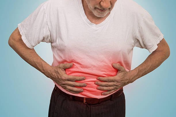Stomach ache, man placing hands on the abdomen stock photo
