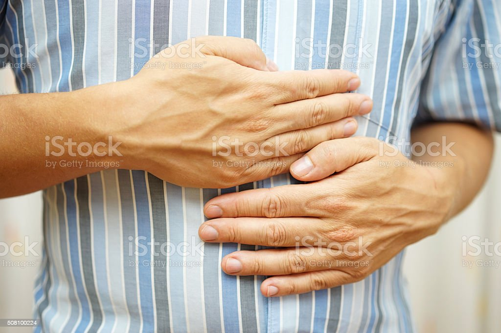 Stomach ache, man placing hands on the stomach, concept of .stomach ulcer stock photo