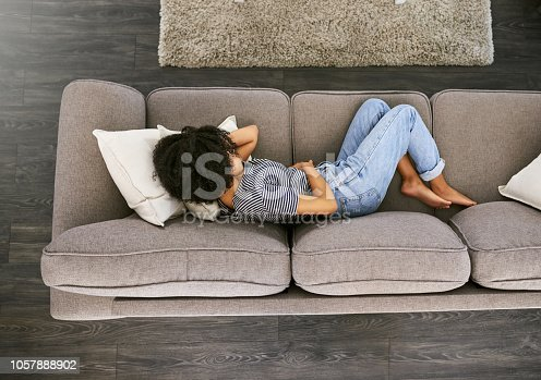 High angle shot of a young woman experiencing stomach pain on the sofa at home