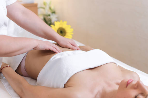 Stomach massage at beauty salon stock photo