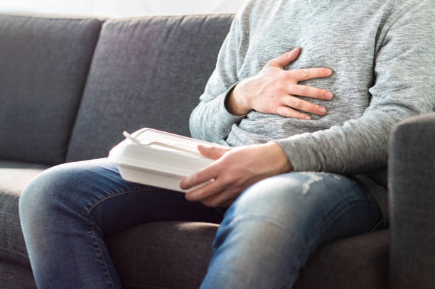 Stomach pain, food poisoning or digestion problem after fast junk food. Man ate too much and is holding belly with hand. stock photo