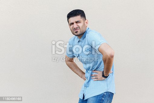 istock Stomach pain or diet problem. Portrait of sick handsome young bearded man in blue shirt standing and holding his painful belly, feeling bad. 1150495165