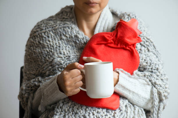 Stomachache Woman having stomachache, holding with hot water bottle on white background. hot water bottle stock pictures, royalty-free photos & images
