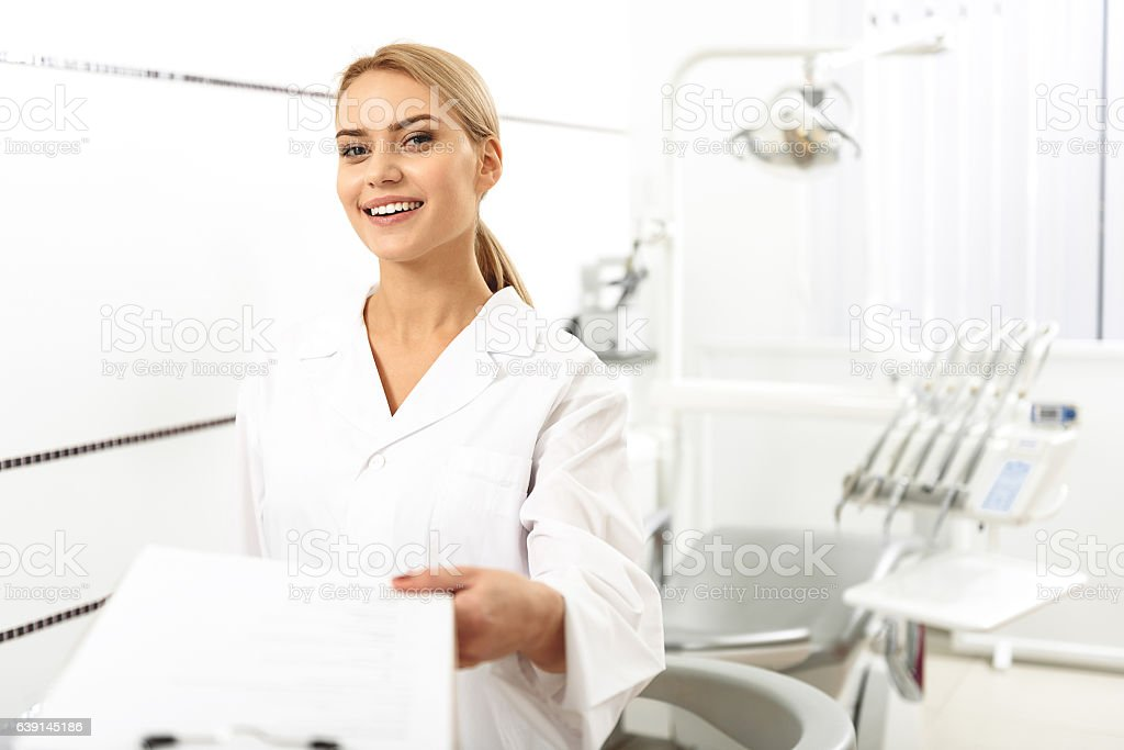 Stomatologist giving blank to her client in office - 1人のロイヤリティフリーストックフォト