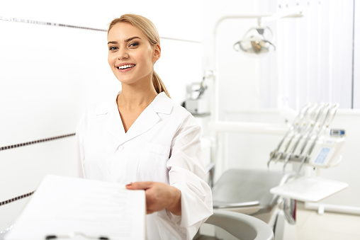 Stomatologist Giving Blank To Her Client In Office - 1人のストックフォトや画像を多数ご用意