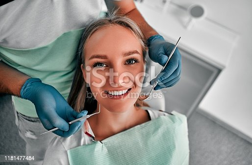 Perfect smile! Part of dentist examining his beautiful patient in dentist's office.