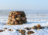 istock Stone altar near the frozen river in cold sunny winter morning. 1306099241