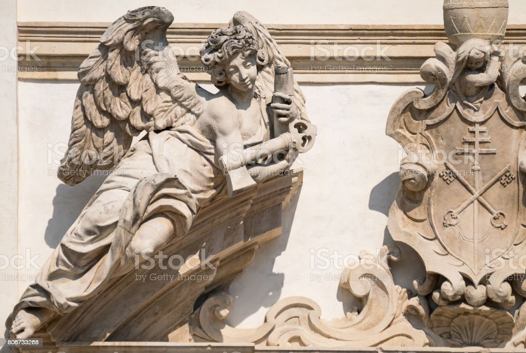 Stone angel on the facade of a medieval church. stock photo