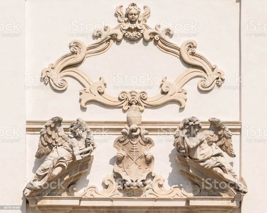 Stone angels on the facade of a medieval church. stock photo