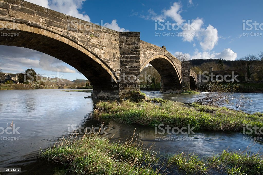 Stone Arch Bridge Across River on Sunny Day stock photo