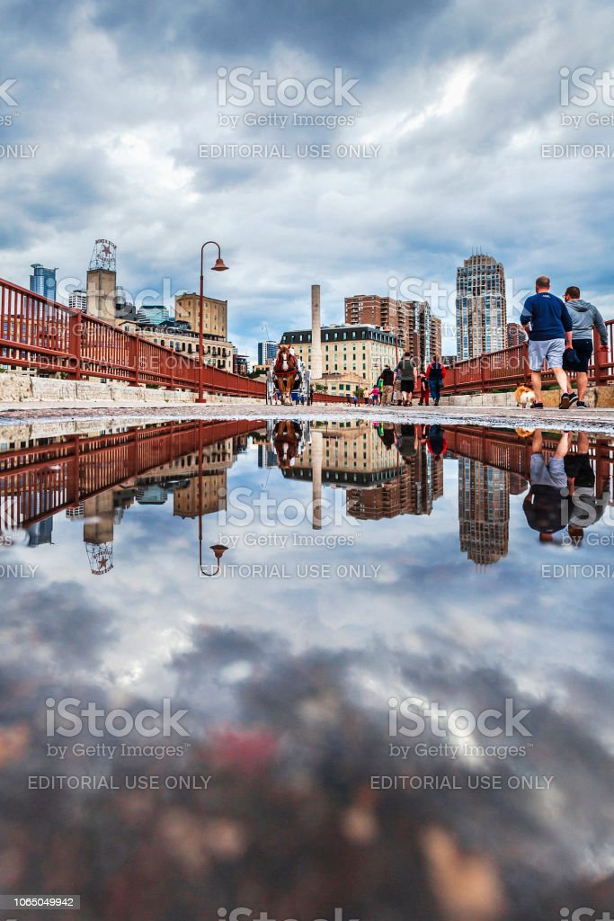 Stone Arch Bridge in Minneapolis reflected in puddle stock photo