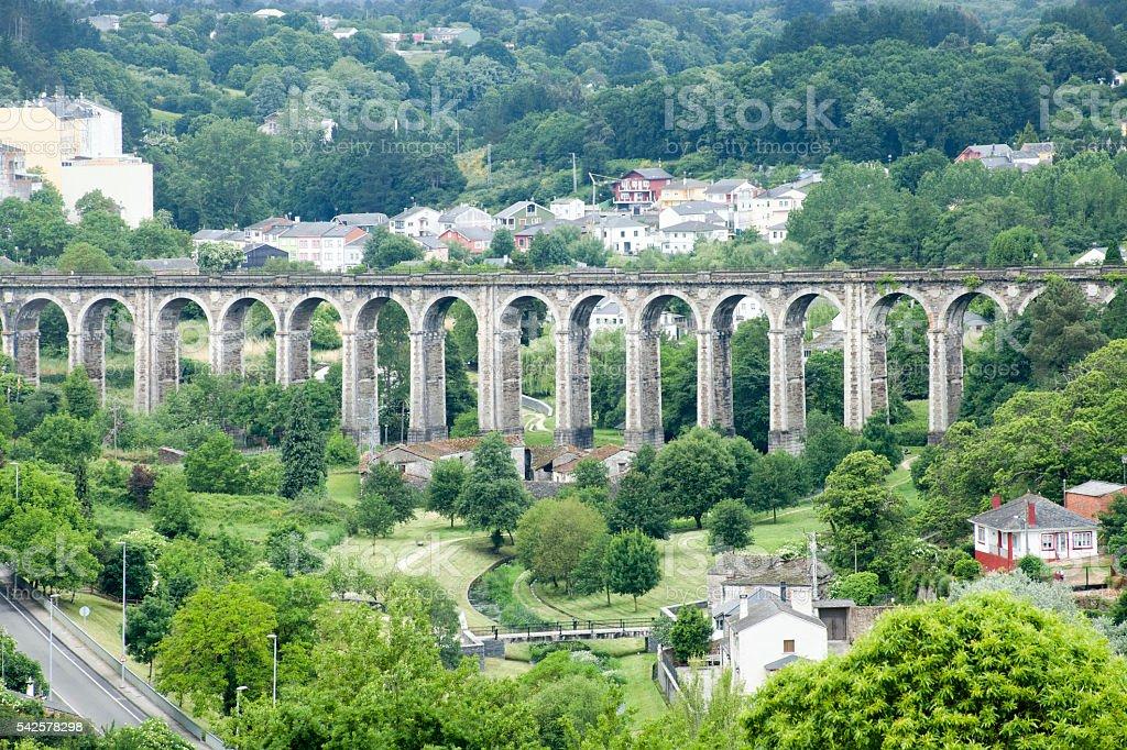 Stone arch railway bridge and green landscape. stock photo