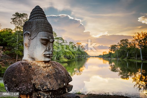 istock Stone Asura and sunset over moat surrounding Angkor in Cambodia 589972408