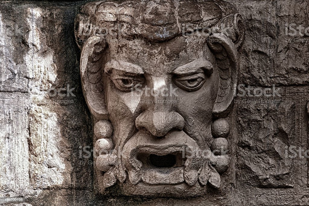 Stone bas-relief a kind of a head of a demon stock photo