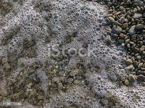 istock Stone beach background with sea foam 1136773160