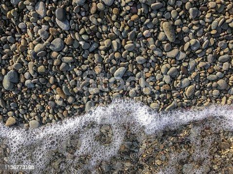 istock Stone beach background with sea foam 1136773198