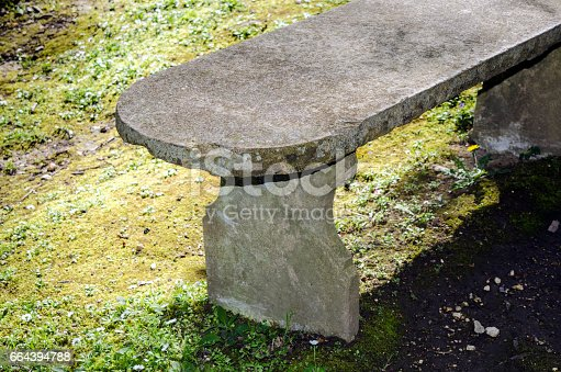 Empty stone bench, with a grass area on the background.