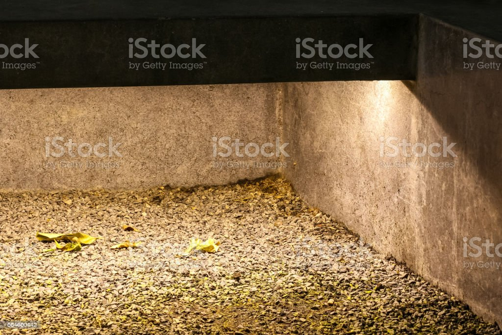 stone bench with light underneath along with grass field in the night stock photo