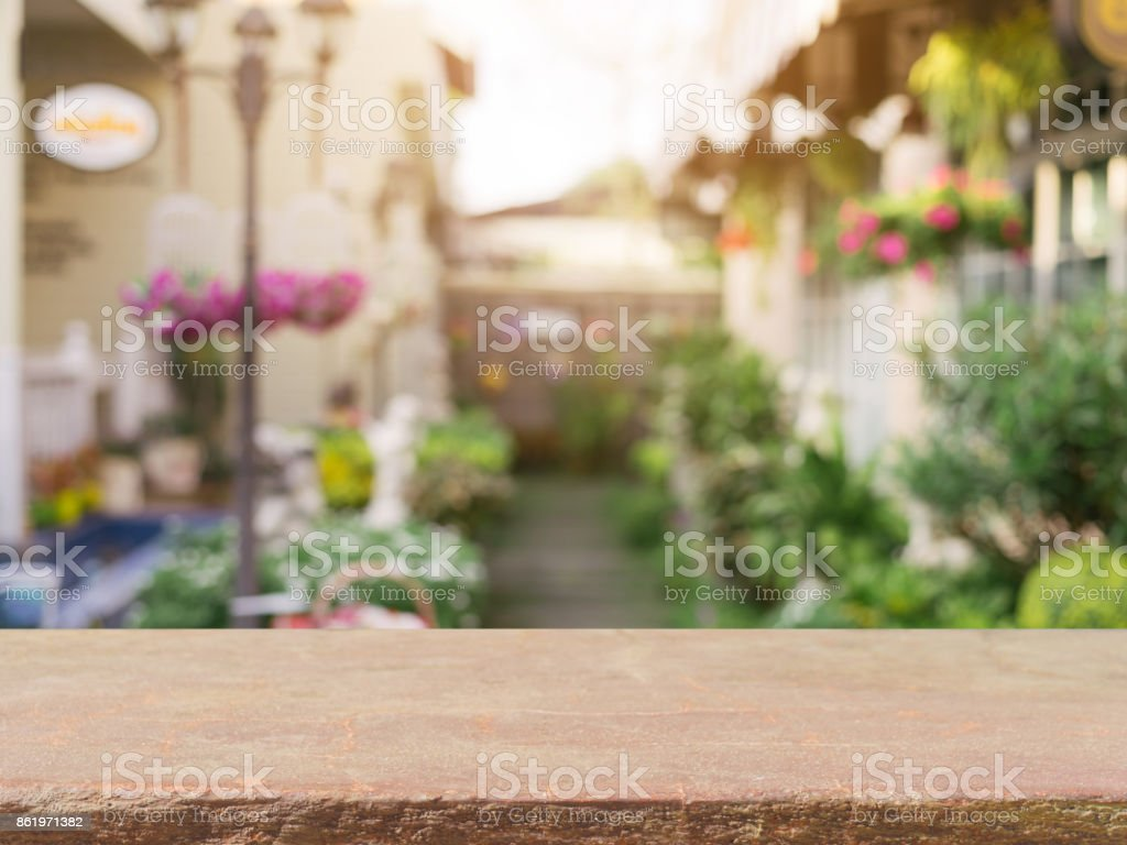 Stone board empty table in front of blurred background. Perspective brown stone over blur in coffee shop - can be used for display or montage mock up your products. vintage filtered image. stock photo