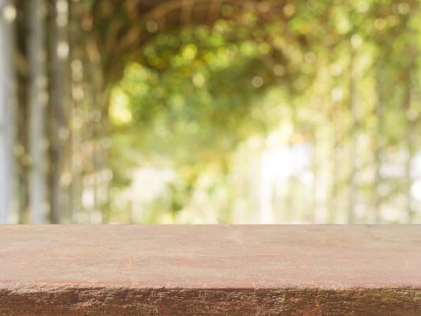 stein brett leer tischplatte vor unscharfen hintergrund. perspektive braunen stein tischplatte über bäume im wald zu verwischen - eignet sich für display oder montage ihrer mock-up produkte. frühjahrssaison. - naturstein terrasse stock-fotos und bilder
