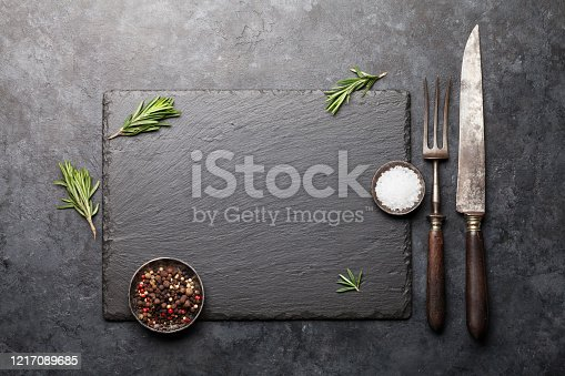 Stone board with spices, herbs, utensils and copy space for your menu, recipe or dish. Top view flat lay