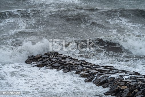 Waves crash into the breakwater