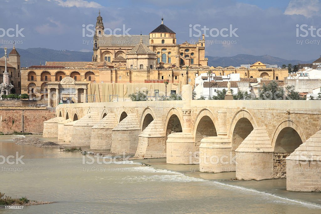 A stone bridge and buildings on a cloudy day in Ce_rdoba royalty-free stock photo