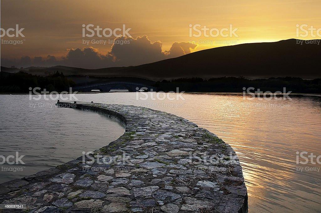 Stone bridge on the calm water of  lake royalty-free stock photo