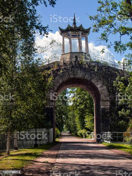 Photo of Stone bridge tunnel over the road with a Chinese-style gazebo in the Alexander Park in Tsarskoye Selo in St. Petersburg