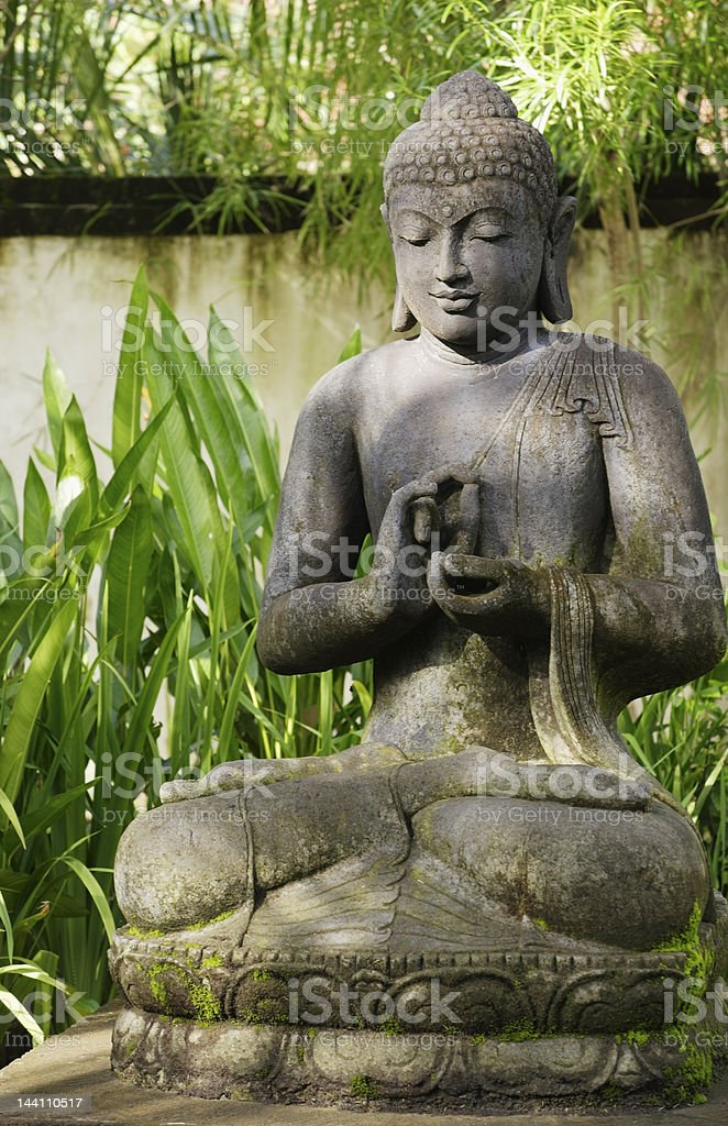 Stone Buddha in tropical garden royalty-free stock photo