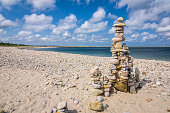A carefully constructed stone cairn on a beach near the eastern entrance of the Cape Cod Canal consists of delicately balanced smooth beach stones.