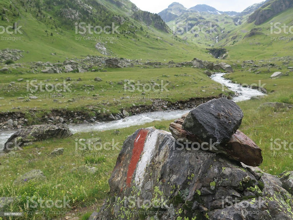 Stone Cairn red and white paint on rocks in mountain stock photo