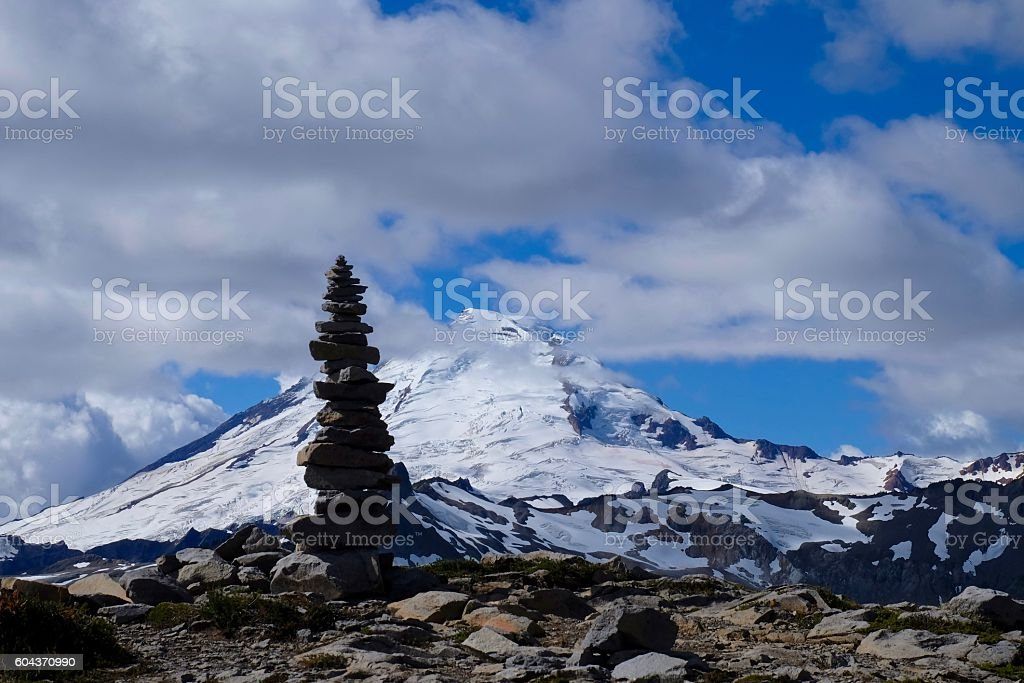 Stone cairn sihouette against glacier on mountain top. stock photo