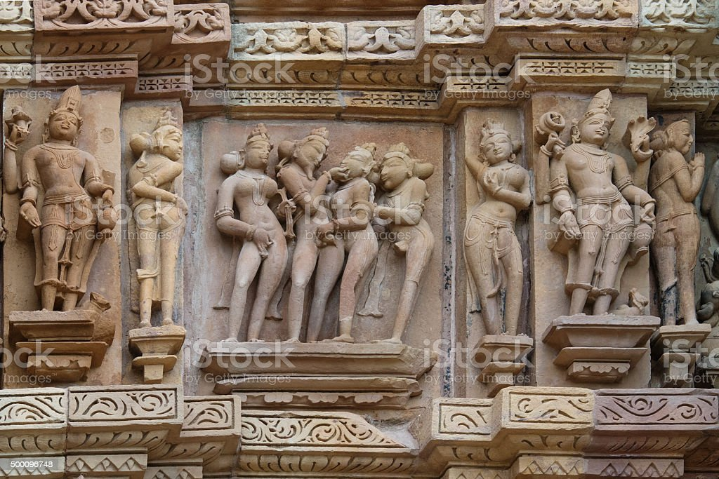 Stone carved erotic bas-relief in Hindu temple in Khajuraho, India. stock photo