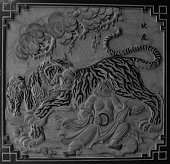 Stone carving of a tiger fighting a man at a Chinese temple