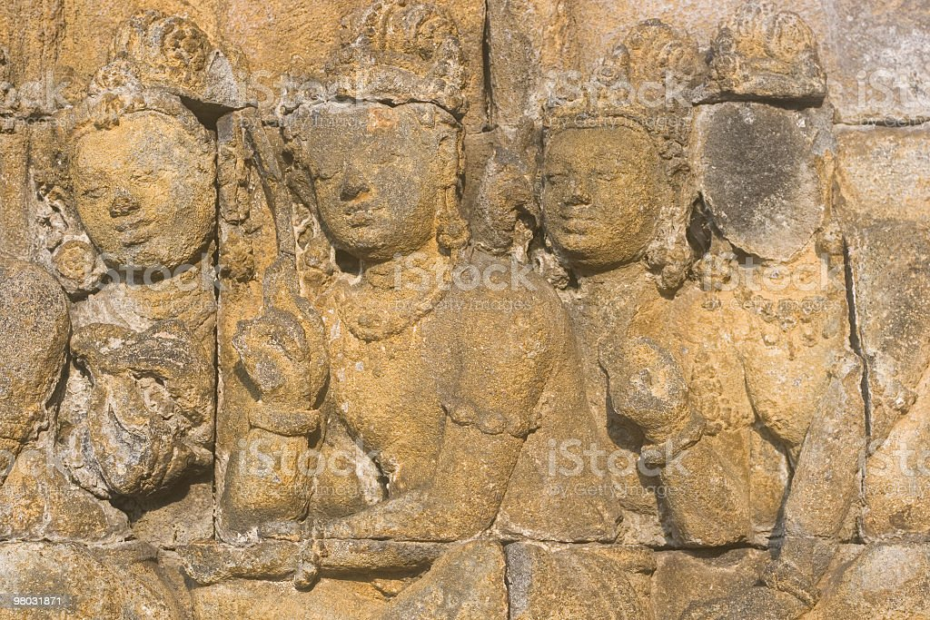 Stone carving of four persons at Buddhist temple in Indonesia. royalty-free stock photo