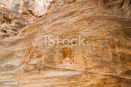 Stone carving on the wall of siq canyon in Petra, Jordan.