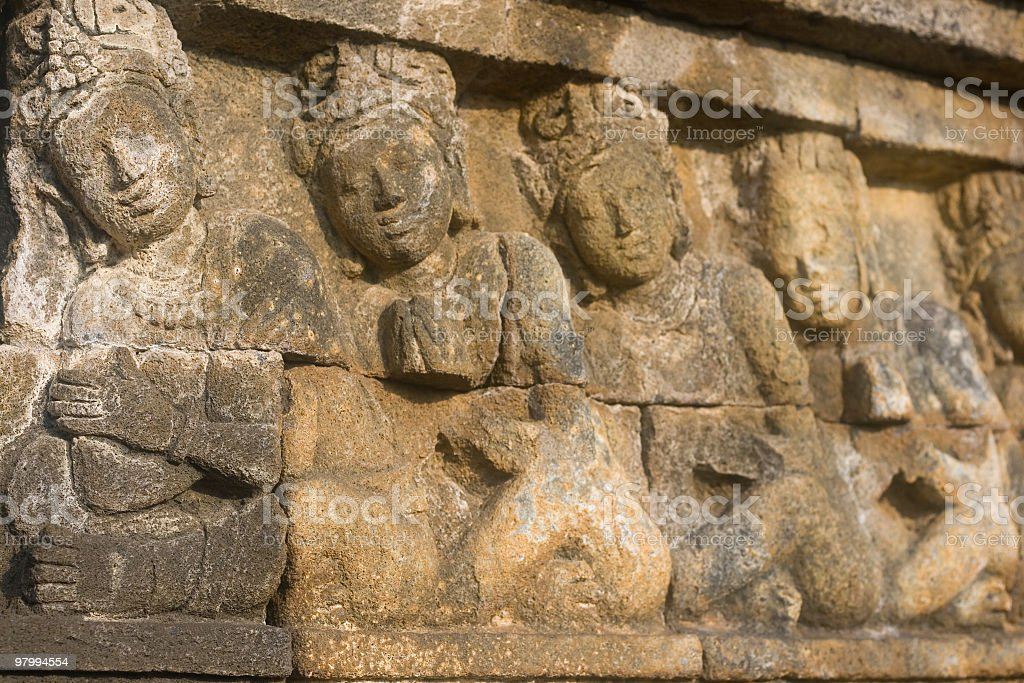 Stone carving showing four ancient figures. royalty-free stock photo