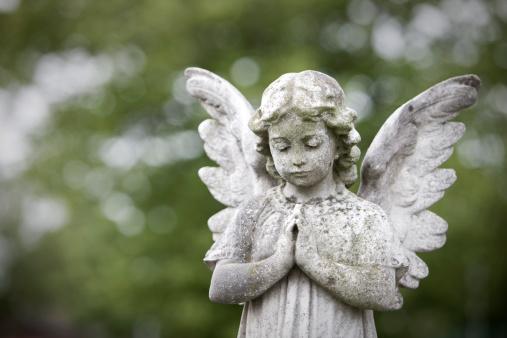 Stone cherub praying
