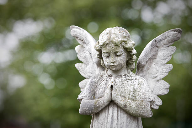 Stone cherub praying stock photo