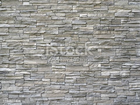 Stone cladding wall made of  striped stacked slabs of natural gray rocks. Panels for exterior. Background and texture.